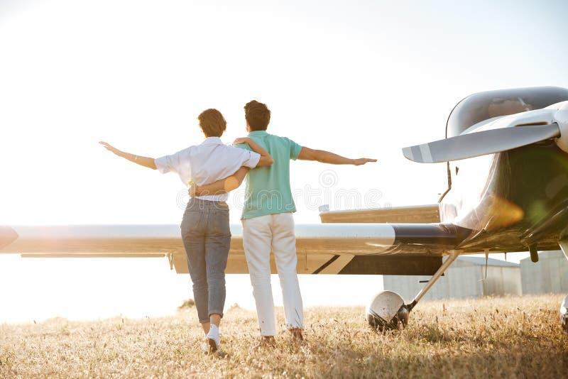 Tillbaka sikt av par som går på fält nära det lilla flygplanet arkivfoto