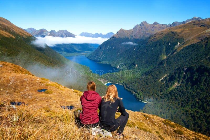Tillbaka sikt av parhandelsresande framme av att bedöva sikten för bergdalsjö, nyckel- spår för toppmöteruttbrännskada, Fiordland royaltyfri bild