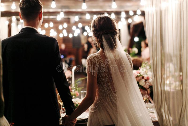 Tillbaka sikt av romantiska par av bruden och brudgummen på banketthanden - i - hand Ljusen av den elektriska girlanden exponerar royaltyfria bilder