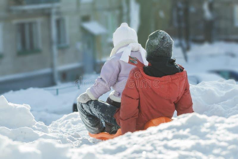 Tillbaka sikt av siblingbarn som är klara att rida den sluttande vintern på den orange plast- snöglidaren utomhus arkivfoto