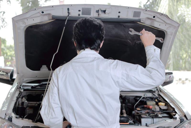 Tillbaka sikt av skiftnyckeln för innehav för motorfordonmekanikerman mot bilen i öppen huv fotografering för bildbyråer