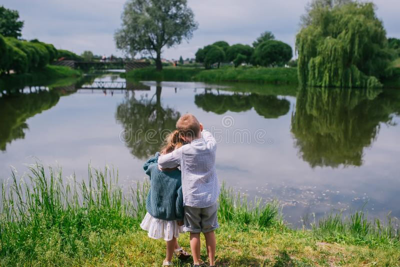 Tillbaka sikt av små barn som ser sjön på sommardag arkivbilder