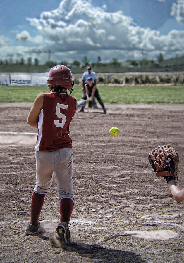 Tillbaka sikt av softballspelaren efter svängande slagträ royaltyfri bild