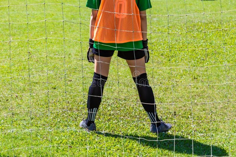 Tillbaka sikt av stading vänta för ung kvinnlig goalie framme av H royaltyfria foton