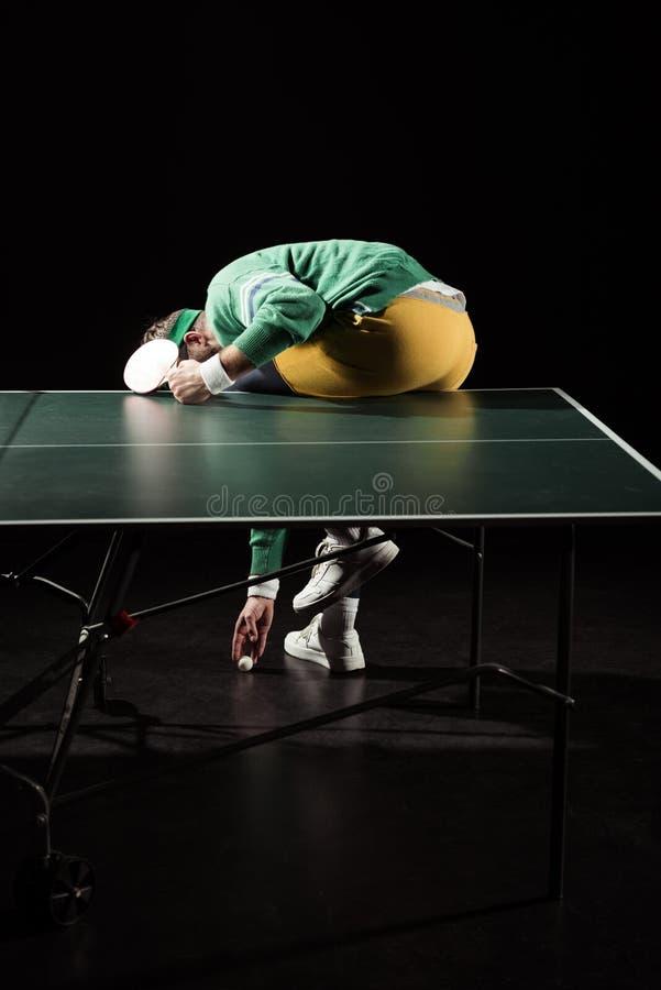 tillbaka sikt av tennisspelaren som upp väljer bollen, medan sitta på tennistabellen royaltyfri fotografi