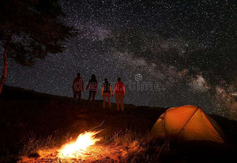 Tillbaka sikt av två händer och att tycka om för parinnehav den mjölkaktiga vägen på stjärnklar himmel under natt av att campa royaltyfri foto