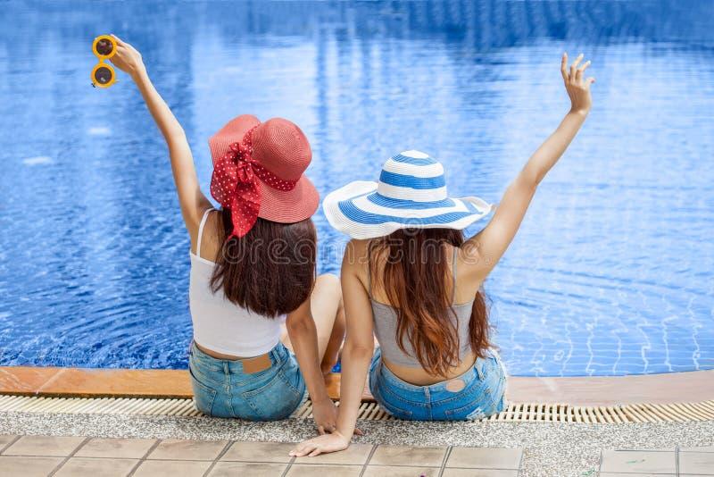 Tillbaka sikt av två härliga unga asiatiska kvinnor i stor sommarhatt och solglasögon som sitter på kanten av simbassängen med fo arkivfoton