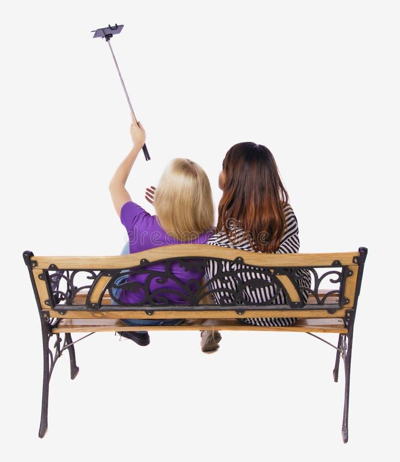 Tillbaka sikt av två kvinnor som gör en selfie att klibba ståendesammanträde på bänken royaltyfri bild