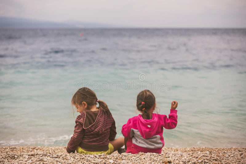 Tillbaka sikt av två små flickor som sitter nära havet arkivbild