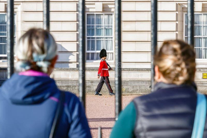 Tillbaka sikt av två turister som håller ögonen på en vaktpost av grenadjären Guards patrullera utanför Buckingham Palace arkivfoton
