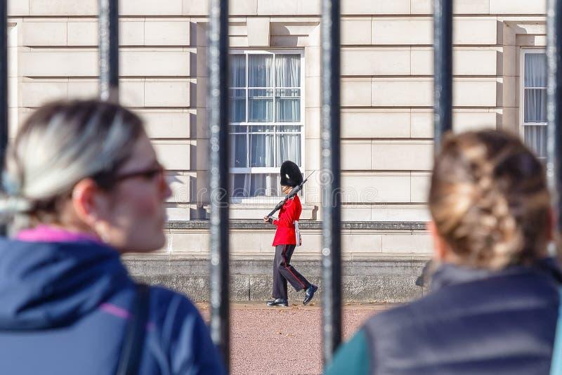 Tillbaka sikt av två turister som håller ögonen på en vaktpost av grenadjären Guards patrullera utanför Buckingham Palace arkivbilder