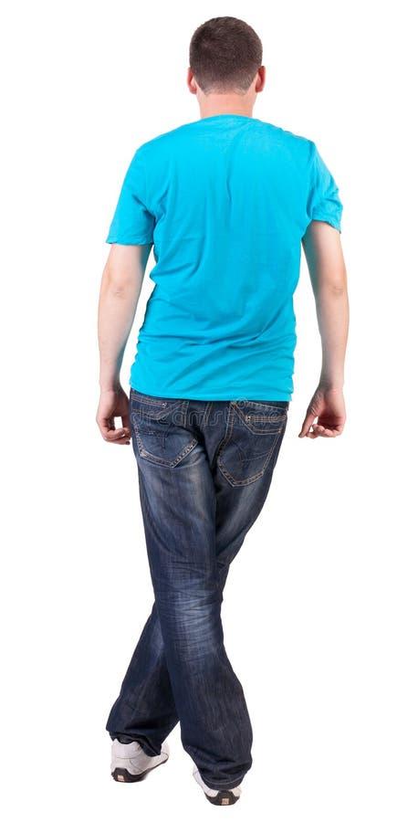 Tillbaka sikt av unga män i blå t-skjorta och jeans arkivfoto