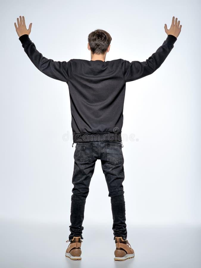 tillbaka sikt Den tonåriga pojken står på studion med lyftta armar royaltyfria foton