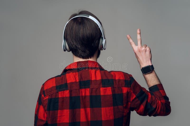 tillbaka sikt lyssnande manmusik för hörlurar till royaltyfri fotografi