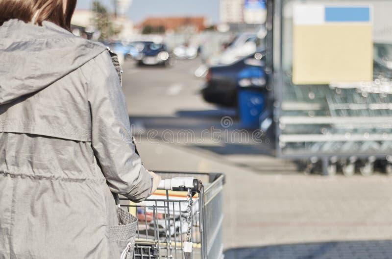Tillbaka sikt med en selektiv fokus av en tonårs- flicka som flyttar en shoppingvagn utanför en supermarket royaltyfri bild