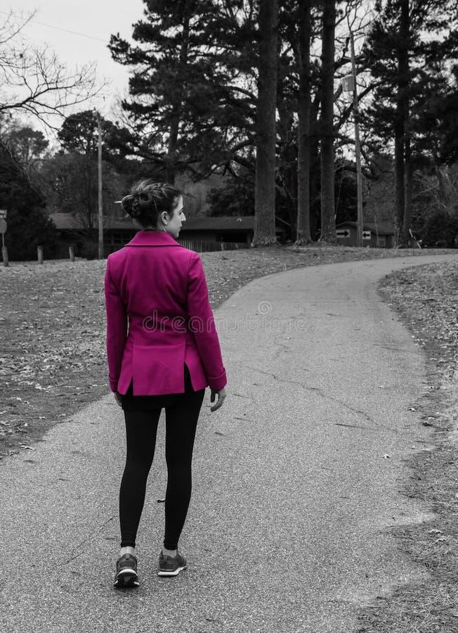Tillbaka sikt, partisk profil som är svartvit av den unga kvinnan som bär det ljusa rosa lagomslaget, flätat hår som går på banan arkivfoto