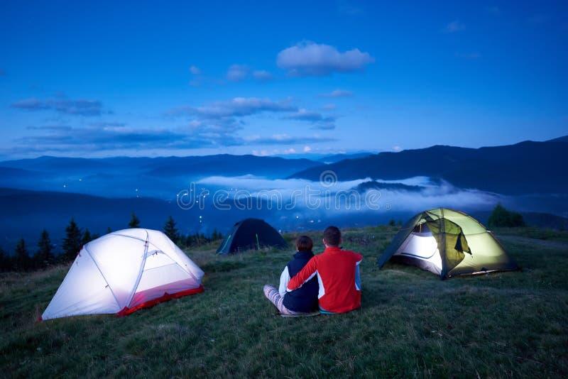 Tillbaka sikt som älskar folk som sitter nära campa tyckande om soluppgång i berg arkivbild