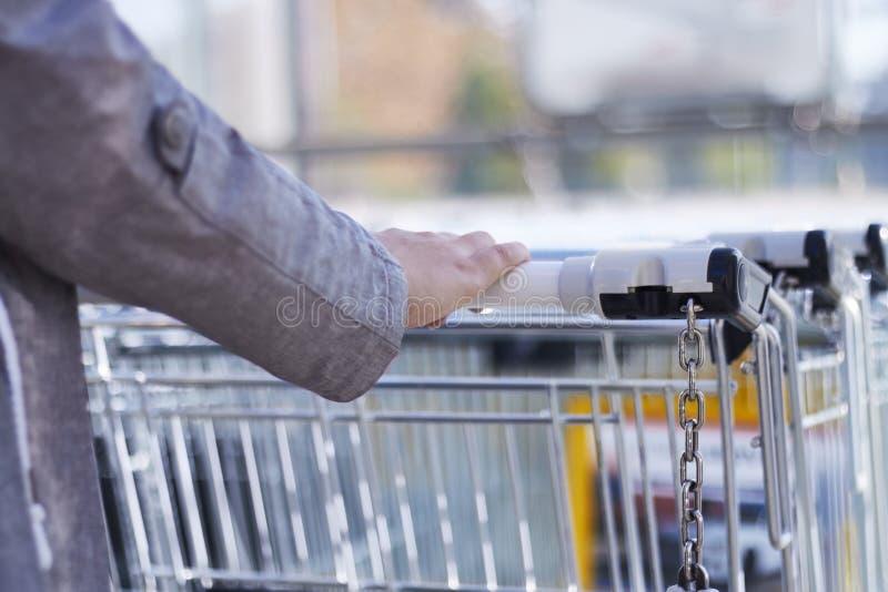 Tillbaka siktscloseup med en selektiv fokus av en flicka som tar en shoppingvagn från en ställning utanför en supermarket royaltyfri fotografi