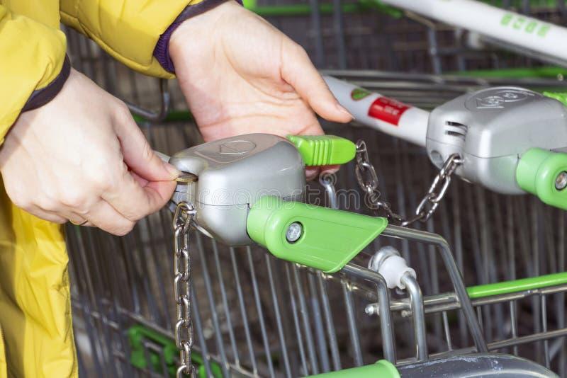 Tillbaka siktscloseup med en selektiv fokus av en flicka som tar en shoppingvagn från en ställning utanför en supermarket arkivfoton