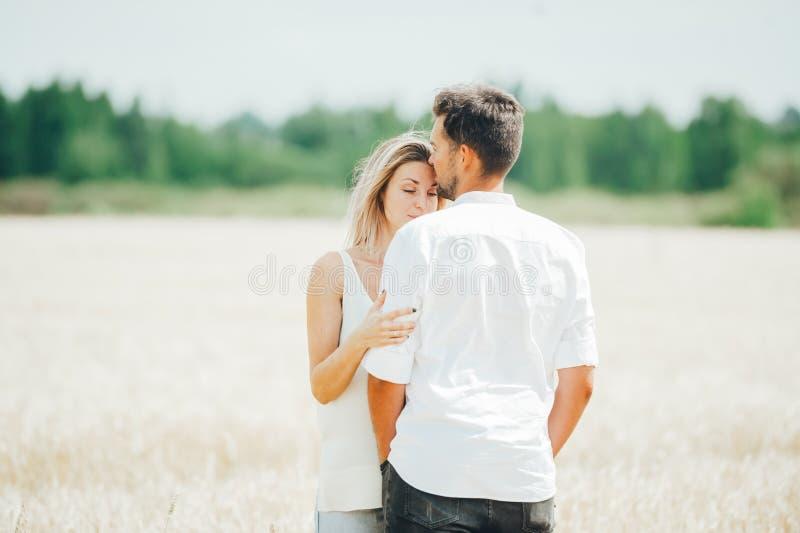 Tillbaka siktscloseupstående av det gulliga älska paranseendet som poserar i vetefält royaltyfri fotografi