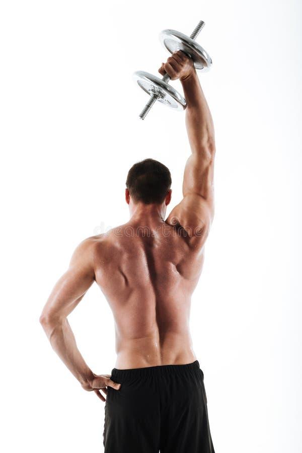 Tillbaka siktsfoto av den starka crossfitmannen som lyfter upp tung hantel royaltyfri bild