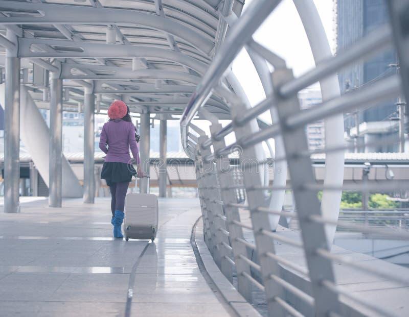 Tillbaka siktskvinnahandelsresande som går med resväskan på flygplatskorridoren royaltyfri fotografi