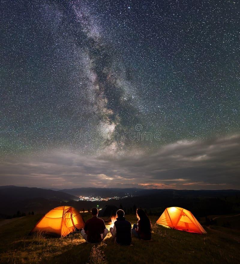 Tillbaka siktslopplag som sitter nära brand bredvid att campa i natt under wonderfullhimmel med många stjärnor royaltyfri bild