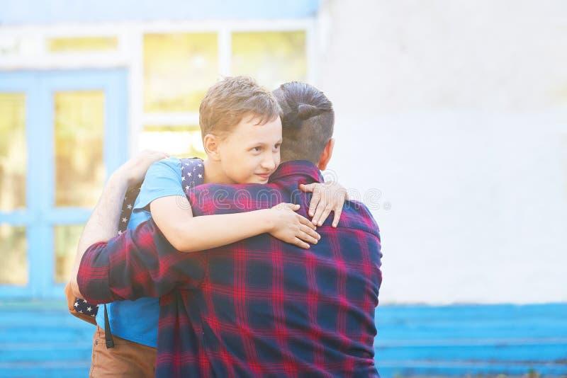 tillbaka skola till Lycklig fader- och sonomfamning framme av grundskolan Föräldern tar barnet till grundskola för barn mellan 5  royaltyfria bilder