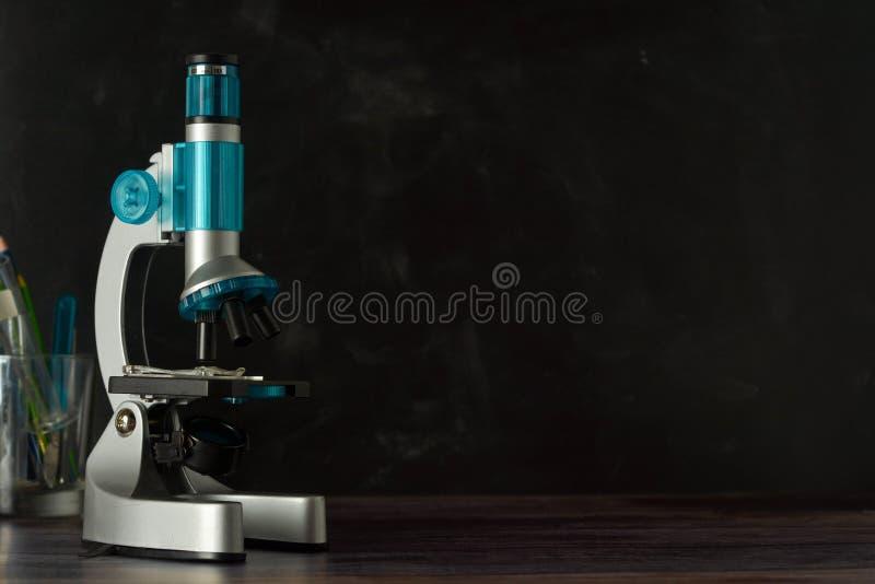 tillbaka skola till Mikroskop som isoleras på svart bakgrund Studera biologi på skolalaboratoriumet royaltyfri foto