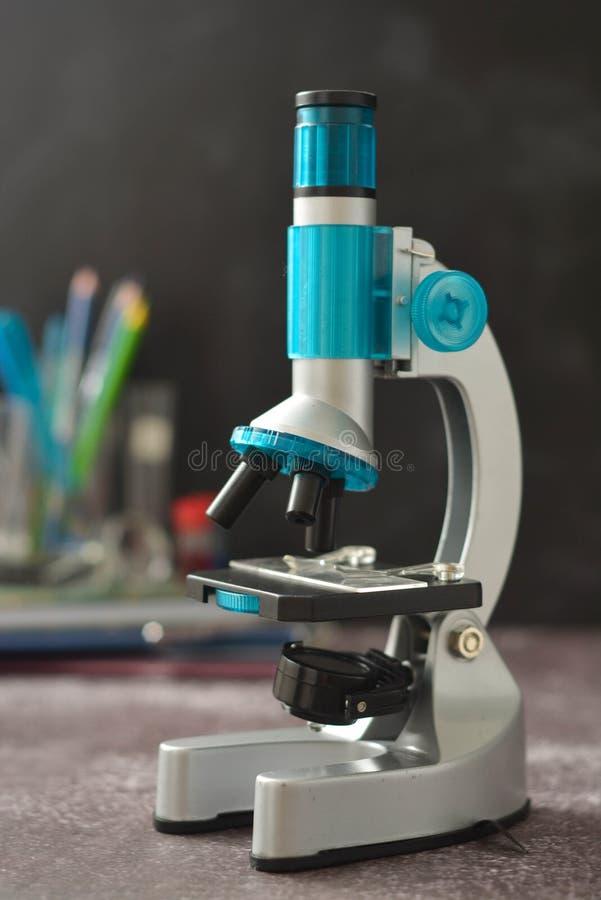 tillbaka skola till Mikroskop som isoleras på svart bakgrund Studera biologi på skolalaboratoriumet arkivfoton