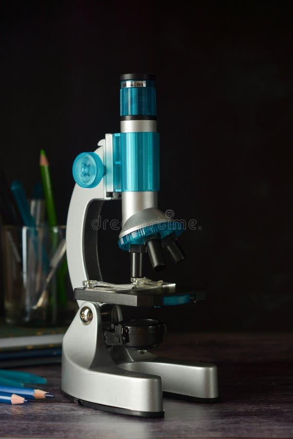 tillbaka skola till Mikroskop som isoleras på svart bakgrund Studera biologi på skolalaboratoriumet arkivbilder