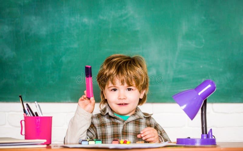 tillbaka skola till preschooler Ungen l?r i grupp p? bakgrund av svart tavla Förskolebarn nära svart tavla fotografering för bildbyråer