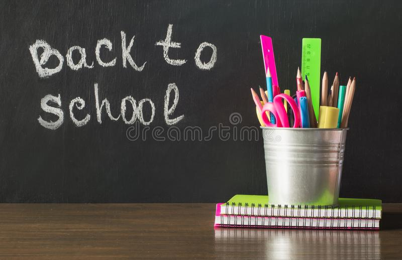 tillbaka skola till Skolatillförsel, förskriftsbok och penna Kopieringsutrymme på den svart tavlan arkivbild
