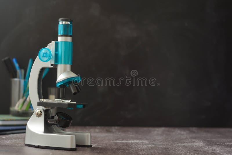tillbaka skola till svart mikroskop f?r bakgrund Studera biologi på skolalaboratoriumet arkivbild