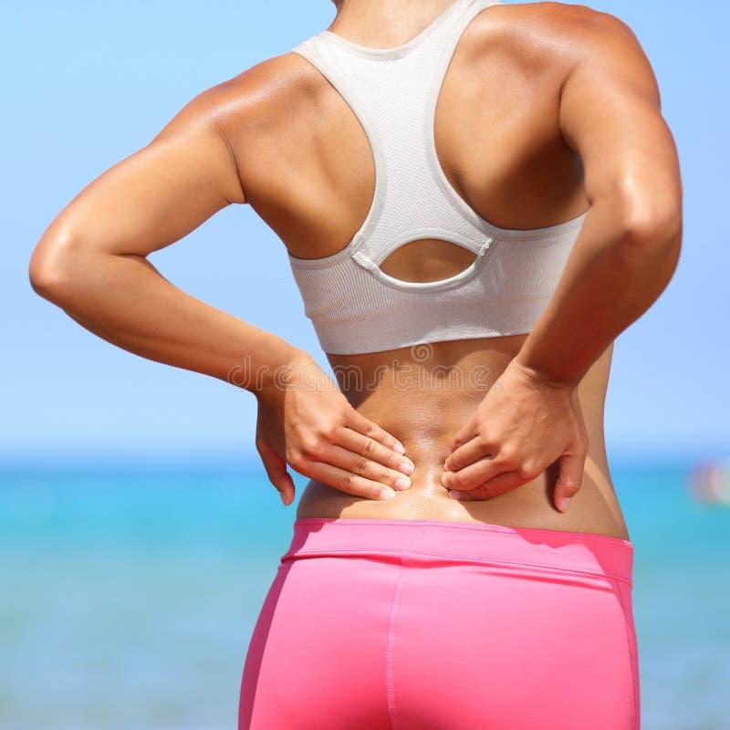 Tillbaka smärta - kvinnan som har skada i lägre baksida royaltyfria bilder