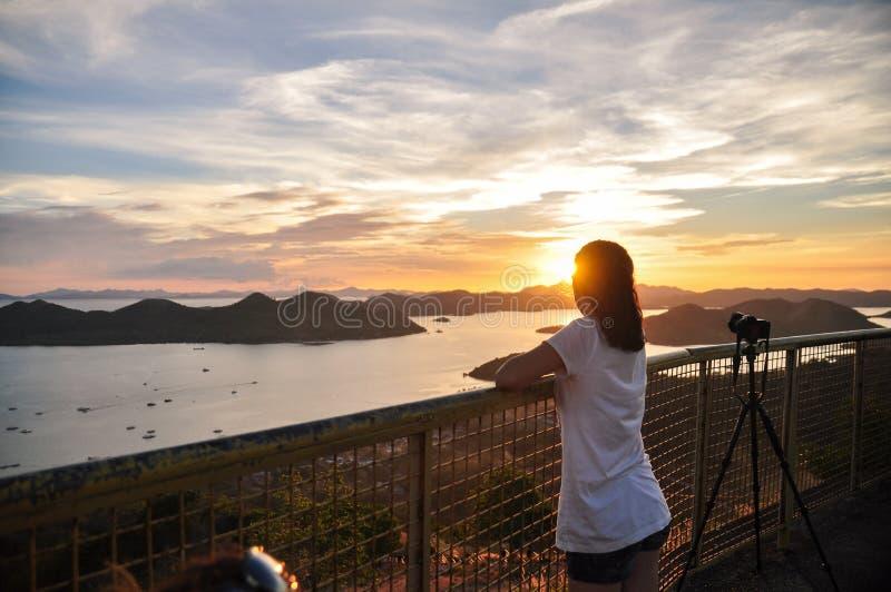 Tillbaka stående av flickan som ser till solnedgången arkivfoto