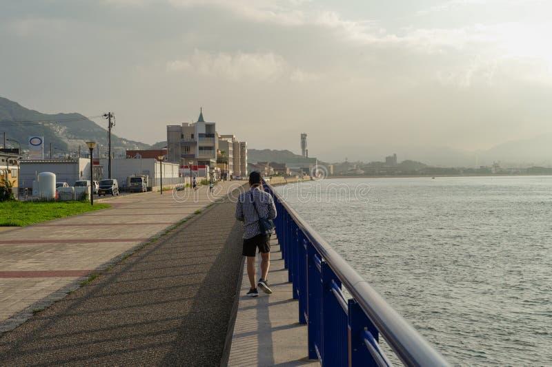 Tillbaka stående av mannen som promenerar fördämningen på sjösidan i den soliga dagen royaltyfri foto