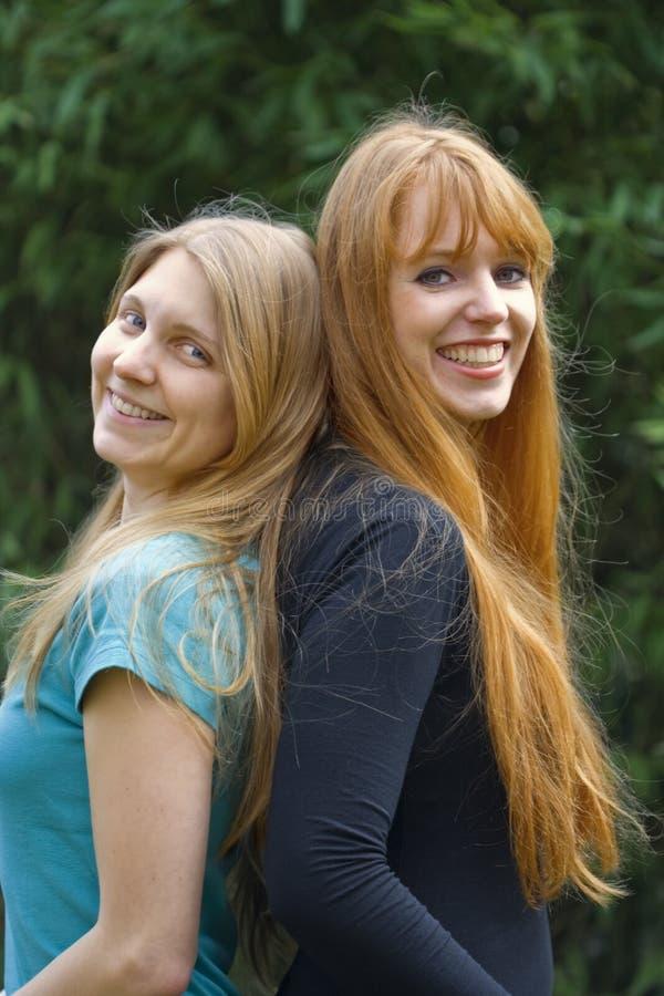 tillbaka standing till två unga kvinnor royaltyfria foton