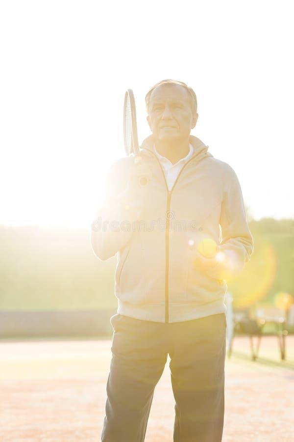 Tillbaka tänt av anseende för hög man med tennisracket och boll mot klar himmel på solig dag royaltyfria foton