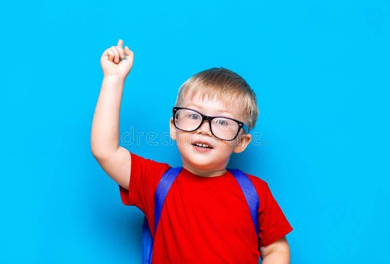 Tillbaka till livsstilen för första kvalitet för skola den yngre Liten pojke i röd t-skjorta Slut upp studiofotoståenden av att l royaltyfria bilder