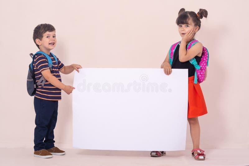 Tillbaka till skola - annonseringar Skolaungar med ryggsäckar som rymmer det vita tomma eller vita kortet royaltyfri foto