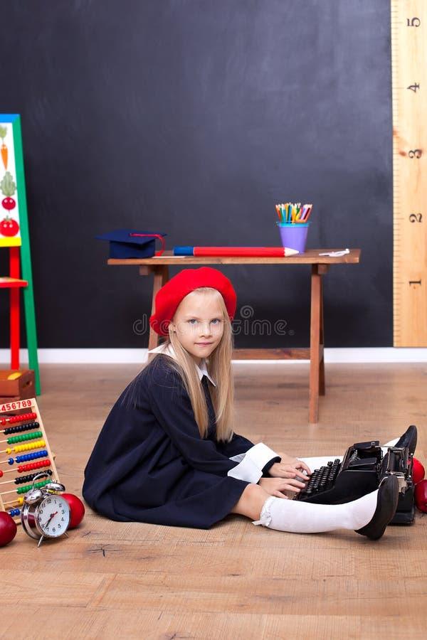 Tillbaka till skola! En flicka sitter på golvet på skola och rymmer en retro skrivmaskin Skolutbildning Liten författare, journal arkivbilder