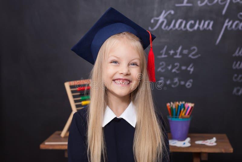 Tillbaka till skola! Gladlynt liten flicka på skola på en svart bakgrund se f?r kamera skola f?r copyspace f?r begrepp f?r svarta arkivfoto