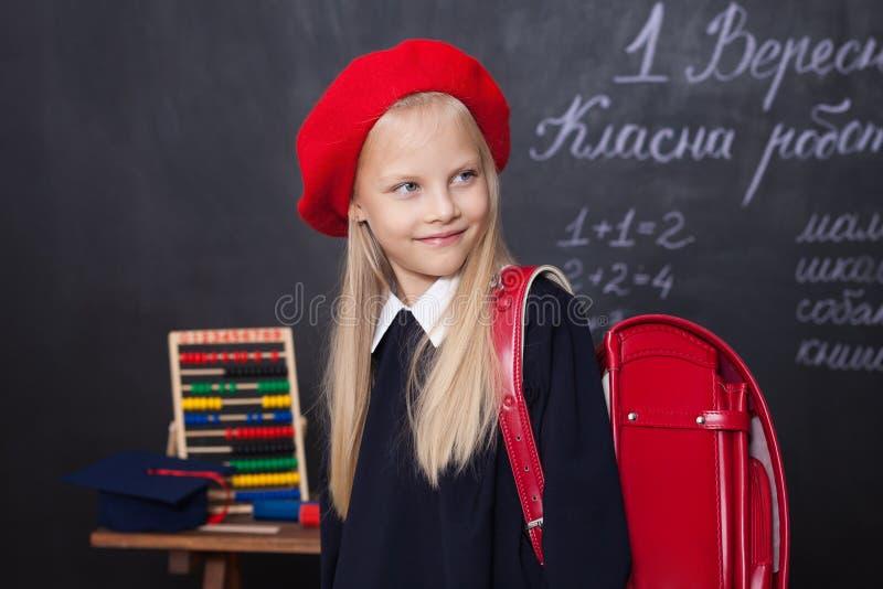 Tillbaka till skola! Lilla flickan står i skola med en röd ryggsäck Skolflickan reagerar till kursen Ungen studerar i clen royaltyfri bild