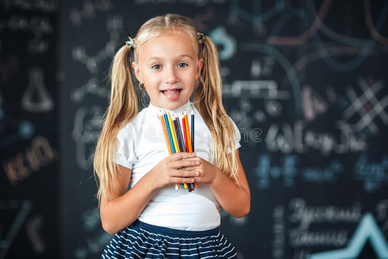 Tillbaka till skola! Lite flickaställningar med blyertspennor i hennes händer mot den svart tavlan med skolaformler på skola Unge royaltyfri bild