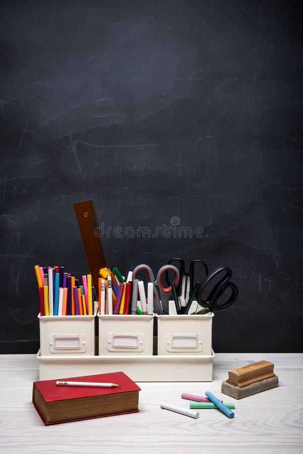 Tillbaka till skolabakgrund med boken, blyertspennor, färgpennor, krita och andra tillförsel på den svarta svart tavlan royaltyfri fotografi
