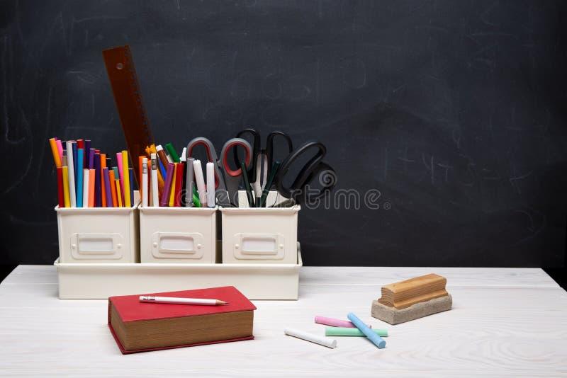 Tillbaka till skolabakgrund med boken, blyertspennor, färgpennor, krita och andra tillförsel på den svarta svart tavlan royaltyfria bilder