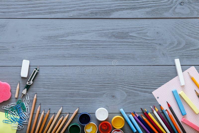 Tillbaka till skolabakgrundsbegreppet med utrymme för fri kopia för text, modern tillförselbrevpapper, färgblyertspennor, målarfä arkivbild