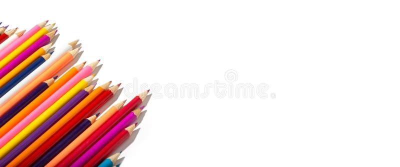 Tillbaka till skolabanret av mångfärgade blyertspennor som isoleras på vit bakgrund arkivfoton