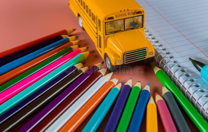 Tillbaka till skolabegreppet med bussen och anteckningsboken, blyertspenna arkivfoton